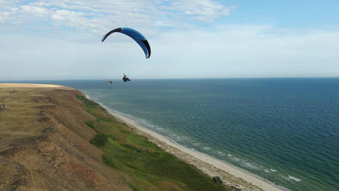 Paragliding extreme sport, people are flying over the sea shore Live Action