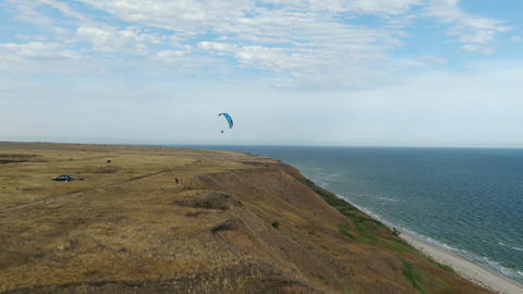 Extreme sports, a man is paragliding over the hills near the sea, aerial shot Live Action