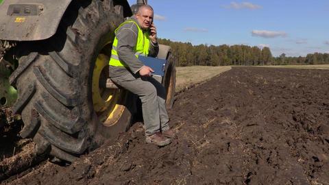 Farmer sitting near tractor wheel and talking on phone Footage