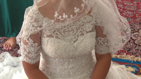 Blond Bride in White under Veil Sits on Carpet in Muslim Mosque Footage