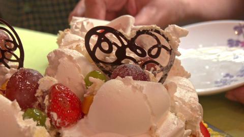 Closeup Hand Cuts Wedding Cake with Chocolate Heart Symbols Footage