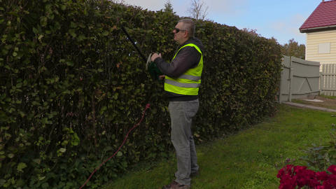 Landscaping worker talking on phone and doing hedge trimmer works Footage