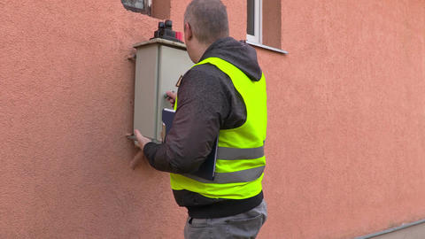 Electrician using tablet near fuse box Live Action