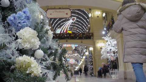 Christmas tree, decorated with decorative flowers, stands in the shopping center Live Action
