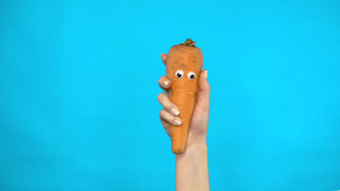 Carrot with eyes in a woman hand close-up. Carrot shakes and twists eyes on a Live Action