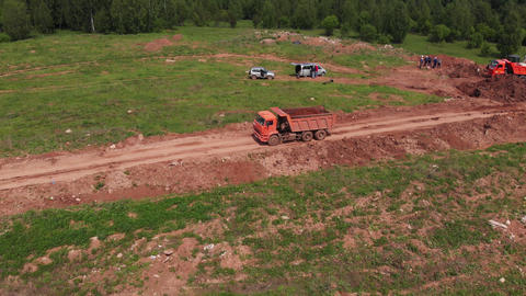 Tipper truck transports dirt from open construction site Live Action