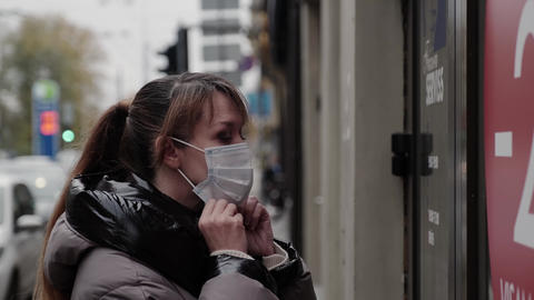 A woman puts on a protective mask before entering the store. Put mask to fight against Corona virus Live Action