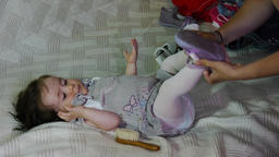 Young mother who shod with a pair of slippers on her daughter sitting supine 85 Live Action
