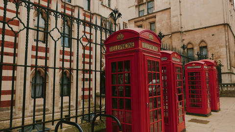 Tilting shot of the Royal Courts of Justice with three red phone booths in the f Footage