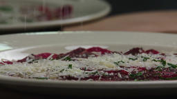 Serving carpaccio meat dish falling parmesan cheese slow motion HD video Footage
