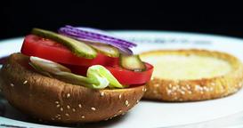 Burger cooking 4k video with copy space. Hamburger ingredients falls bread bun Footage