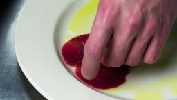 Chef serves carpaccio dish 4k сlose up video. Hand puts raw meat slice on plate Footage