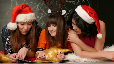 Girls in santa hats are watching the magazine Live Action