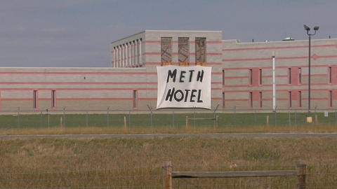 A handmade sign outside a prison reads Meth Hotel Footage