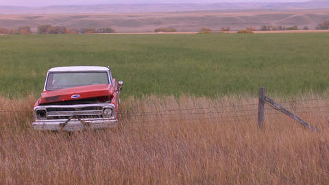 An abandoned pickup truck sits in a field Footage