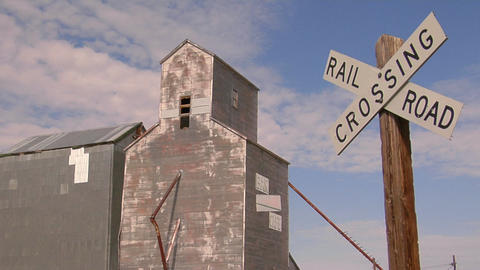 A railroad crossing sign stands near an abandoned grain... Stock Video Footage