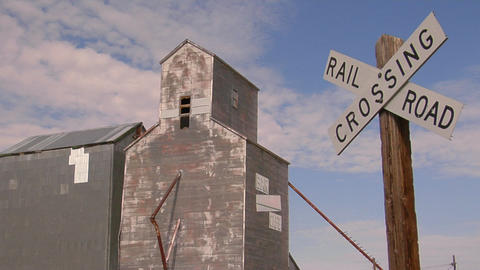 A railroad crossing sign stands near an abandoned grain elevator Footage