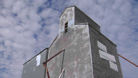"An abandoned grain elevator with a sign saying Bar/Cafe"" stands beneath a blue sky Footage"