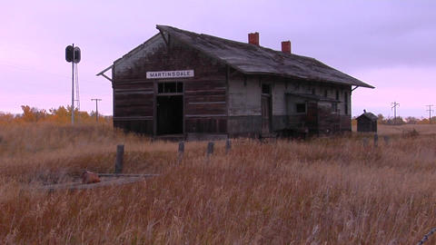 An old station house sits in a field near a railroad track Stock Video Footage