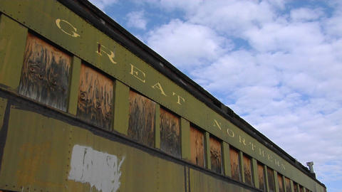 "An abandoned Great Northern"" railway car sits in front of a blue sky and clouds Footage"
