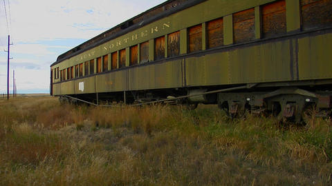 An old abandoned Pullman railway car sits in a field on a lonely stretch of railroad track Footage