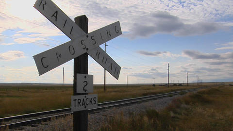 A railroad crossing sign rests stand next to old train... Stock Video Footage