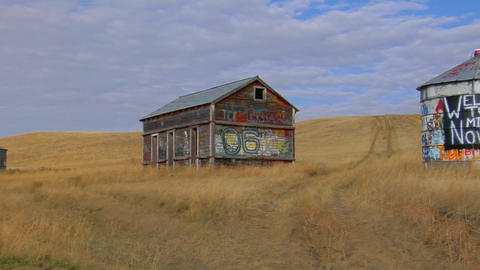 An old abandoned house and water tower with graffiti stand in an open prairie Footage