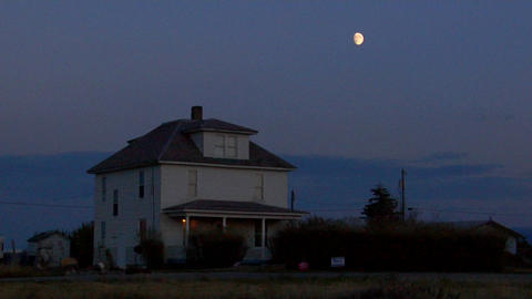 The moon rises over a two story house in the countryside Stock Video Footage