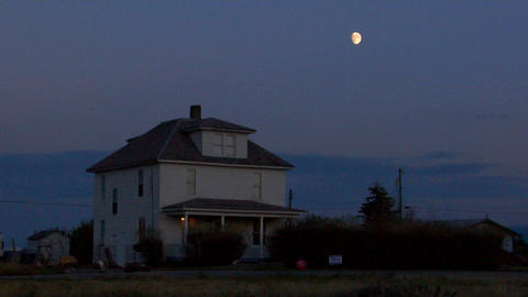 The moon rises over a two story house in the countryside Footage