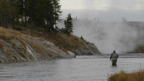 A fly fisherman casts his line into a flowing river Stock Video Footage