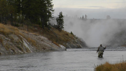 A fly fisherman casts his line into a flowing river Footage