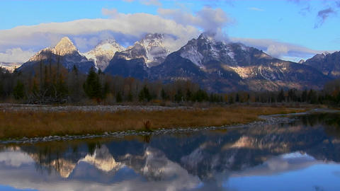 The Grand Teton mountains are perfectly reflected in a mountain lake Footage