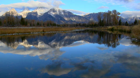 The Grand Teton mountains are reflected in a mountain lake Stock Video Footage