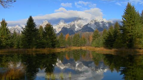 The Grand Teton mountains are reflected in a lake Footage