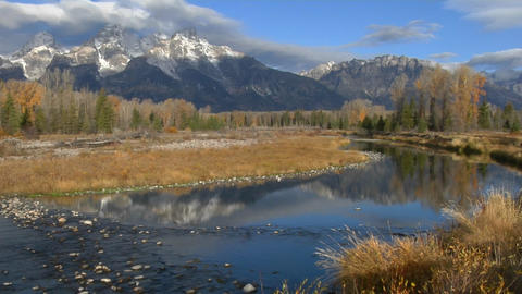 The Grand Teton mountains are reflected in a mountain river Footage