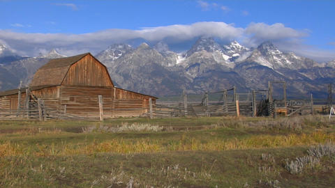 An old barn rises out of a prairie with the Grand Tetons in the background Footage