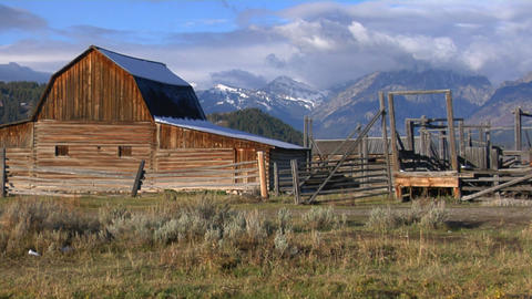 An old barn rises out of a prairie with the Grand Tetons... Stock Video Footage
