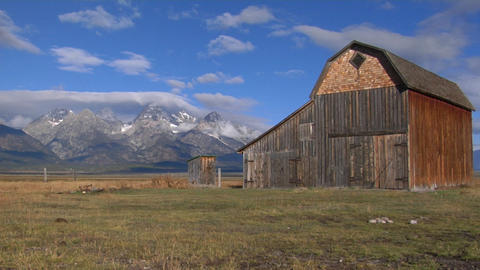 An old barn sits in a field with the Grand Teton mountain... Stock Video Footage