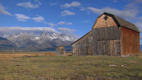 An old barn sits in a field with the Grand Teton mountain Range in the background Footage