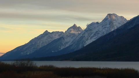 A lake sits below the Grand Teton mountain range Stock Video Footage