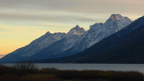 A lake sits below the Grand Teton mountain range Stock Video Footage