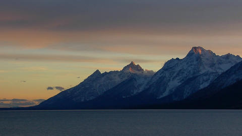 Sunlight glows on the tips of mountain peaks in the Grand Tetons Footage