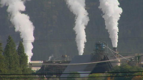 Smoke billows out of three stacks of a factory Stock Video Footage