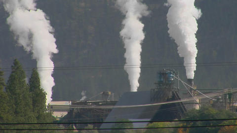 Smoke billows out of three stacks of a factory Footage