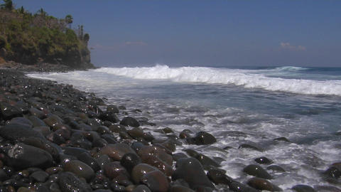 Waves roll onto a rocky beach Footage