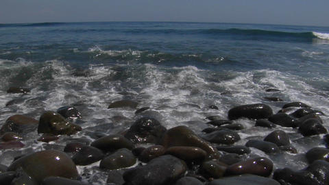 Waves washing over small, smooth rocks on the beach Stock Video Footage