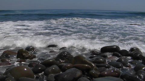 Waves washing over small, smooth rocks on the beach Footage