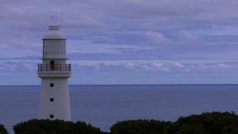 A white lighthouse stands against a blue horizon Stock Video Footage