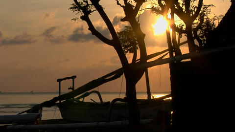The sun sits low on the horizon behind a small fishing... Stock Video Footage