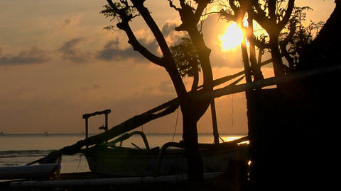 The sun sits low on the horizon behind a small fishing village Footage